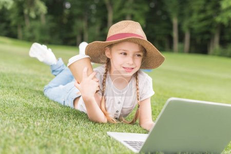 Foto de Niño feliz, sosteniendo la taza de papel y utilizando el portátil mientras se está acostado sobre la hierba en el Parque - Imagen libre de derechos