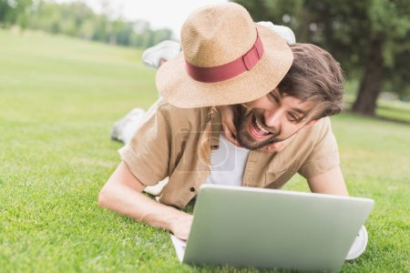 happy father and daughter hugging while using laptop on lawn in park