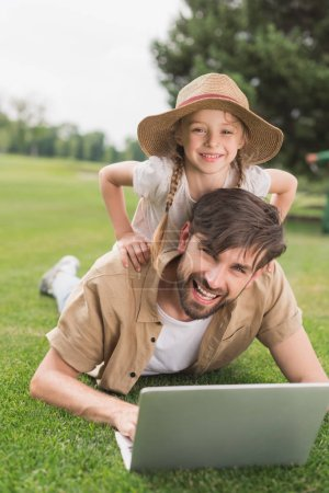 Photo for Happy father and daughter using laptop and smiling at camera in park - Royalty Free Image