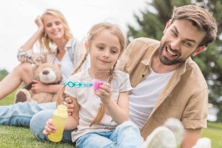 mother with teddy bear looking at happy father and daughter blowing soap bubbles in park