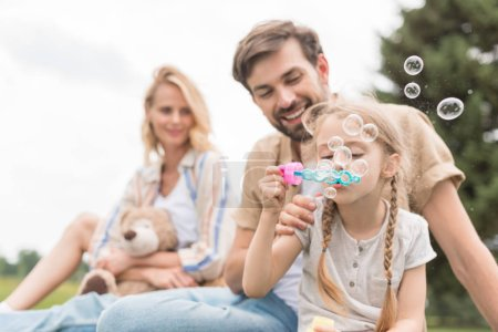 mother holding teddy bear and looking at father and daughter blowing soap bubbles in park