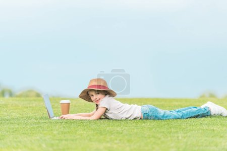 Photo for Adorable child in hat smiling at camera while using laptop on green meadow - Royalty Free Image