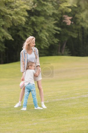 Photo for Happy mother and daughter hugging and looking away in park - Royalty Free Image