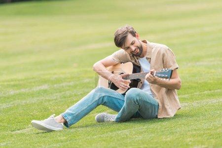 Photo pour Sourire de jeune homme assis sur la pelouse et jouer de la guitare acoustique - image libre de droit