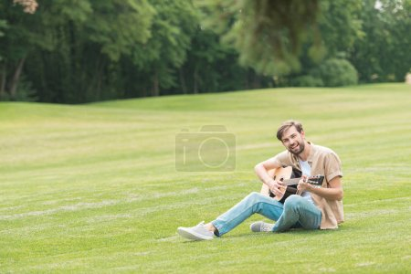 happy young man sitting in green meadow and playing acoustic guitar