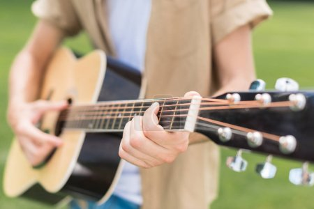 cropped shot of man playing acoustic guitar in park