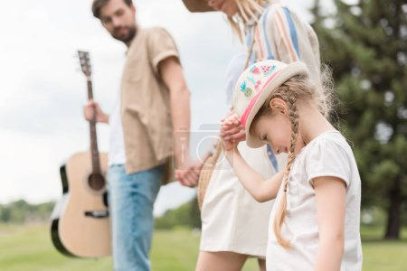 Photo for Cropped shot of parents looking at cute little daughter walking in park - Royalty Free Image