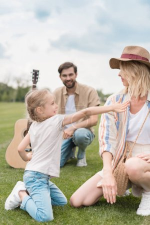 happy mother and daughter smiling each other while father holding acoustic guitar behind in park