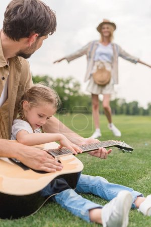 cropped shot of father and daughter playing guitar while mother standing behind on meadow