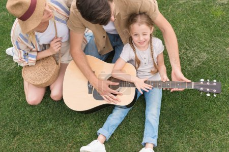 overhead view of family with one child playing acoustic guitar on meadow