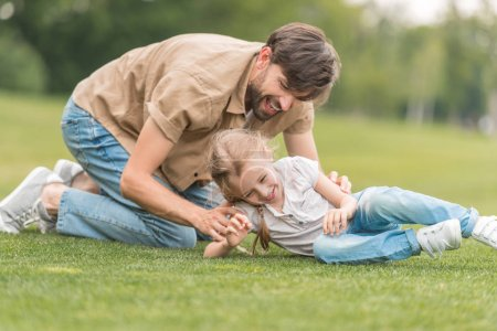 happy father and daughter having fun together on green lawn in park