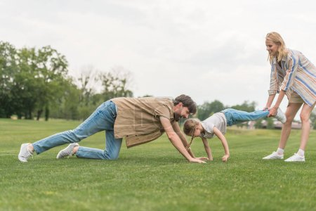 side view of happy family having fun on green grass in park