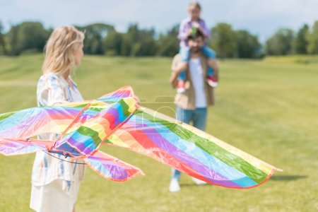 Photo for Young woman holding  kite while father carrying little daughter on neck behind in park - Royalty Free Image