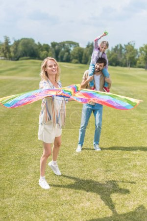 happy parents with cute little daughter playing with colorful kite in park