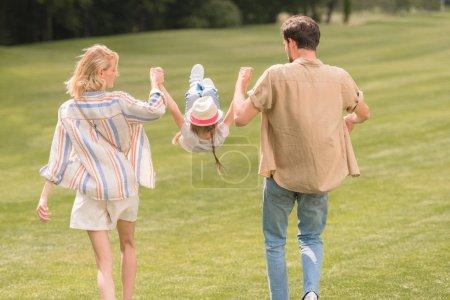 Foto de Vista posterior de los padres con hija cogidos de la mano y que se divierten paseando juntos en el Parque - Imagen libre de derechos