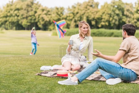 parents sitting in plaid at picnic while daughter lying behind in park