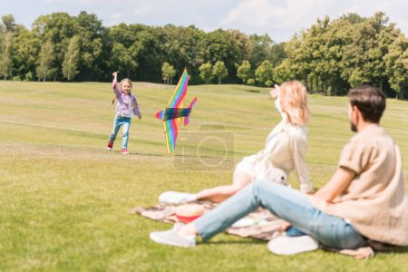 parents sitting on plaid and looking at daughter playing with colorful kite in park