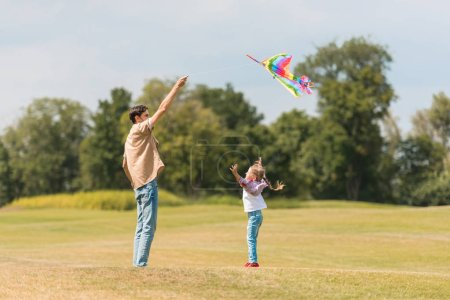 Photo for Side view of happy father and little daughter playing with colorful kite in park - Royalty Free Image