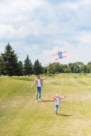 happy father and daughter playing with kite and running on lawn in park