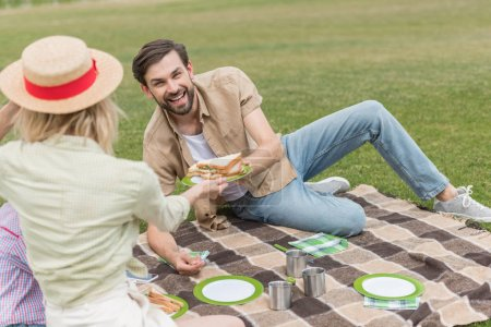 happy family eating sandwiches while sitting on plaid at picnic in park