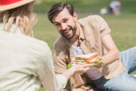 young couple holding sandwiches while spending time together at picnic in park