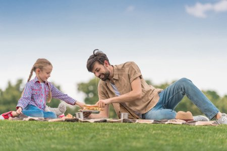 happy father and daughter spending time together at picnic in park