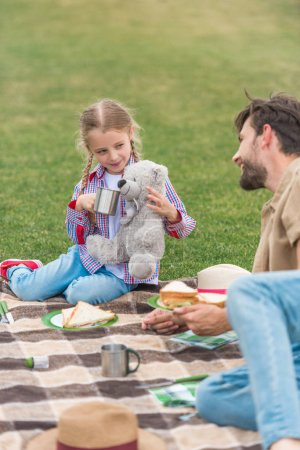 happy father and daughter smiling each other while having picnic in park