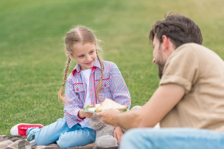 Photo for Happy father and daughter eating sandwiches at picnic in park - Royalty Free Image