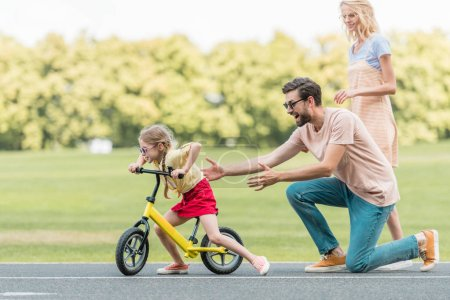Photo pour Vue du côté des parents heureux en regardant mignon petit vélo fille dans le parc - image libre de droit
