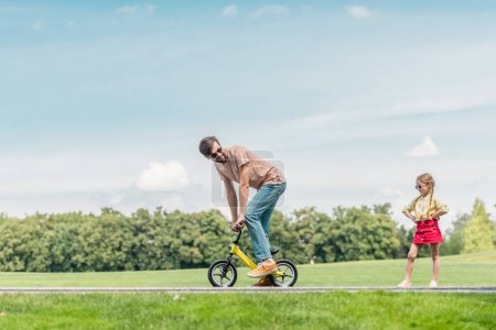 father riding small bicycle and looking at little daughter standing with hands on waist