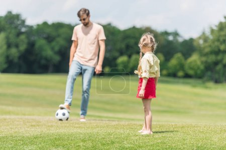 Photo for Father and cute little daughter playing with soccer ball on lawn - Royalty Free Image
