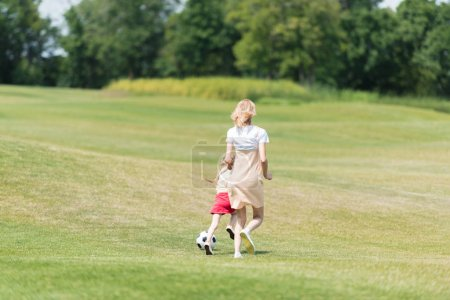 back view of mother and little daughter playing with soccer ball in park