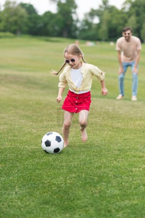 adorable child in sunglasses playing with soccer ball while father standing behind in oark