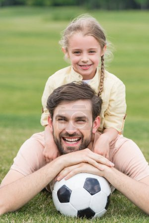 happy father and daughter smiling at camera while lying with soccer ball on grass