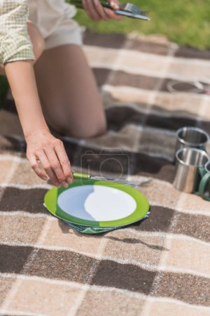 close-up partial view of woman putting cutlery on plaid at picnic