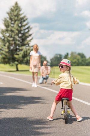 Photo pour Enfant en lunettes de soleil vélo pendant que les parents se tenait derrière dans le parc - image libre de droit