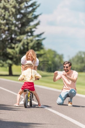 happy young man with smartphone photographing smiling mother teaching daughter riding bicycle in park