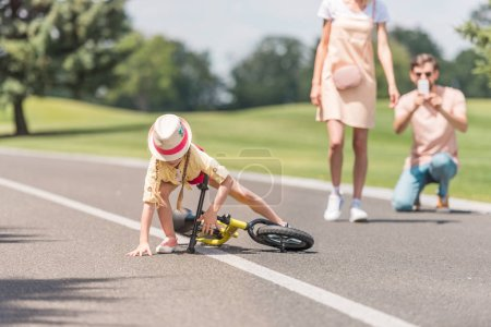 parents photographing little daughter falling from bicycle in park