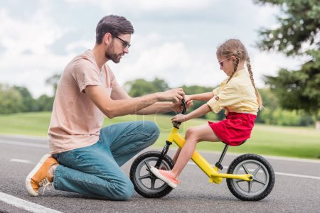 side view of father helping little daughter riding bicycle in park