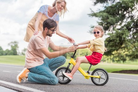 happy parents looking at little daughter riding bicycle in park