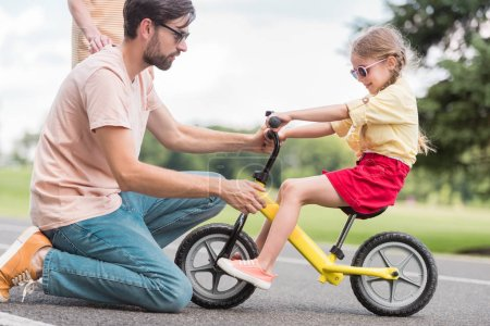 Photo pour Vue latérale du jeune père enseignant petite fille vélo dans le parc - image libre de droit