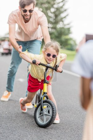 Photo for Happy father helping little daughter riding bicycle in park - Royalty Free Image