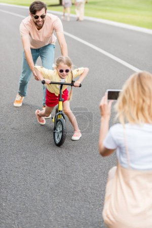 woman with smartphone photographing happy father and daughter riding bicycle in park