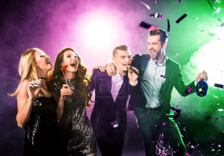 Group of happy friends having fun with champagne bottle and confetti