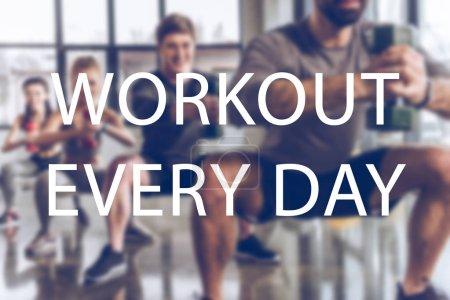 Foto de Grupo borrosa de atléticos jóvenes en ropa deportiva con pesas hacer ejercicio en el gimnasio, entrenamiento todos los días inscripción - Imagen libre de derechos