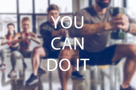 Photo for Blurred group of athletic young people in sportswear with dumbbells exercising at gym, you can do it inscription - Royalty Free Image