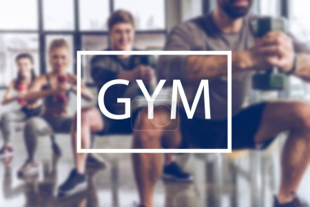 Photo for Blurred group of athletic young people in sportswear with dumbbells exercising at gym, gym inscription - Royalty Free Image
