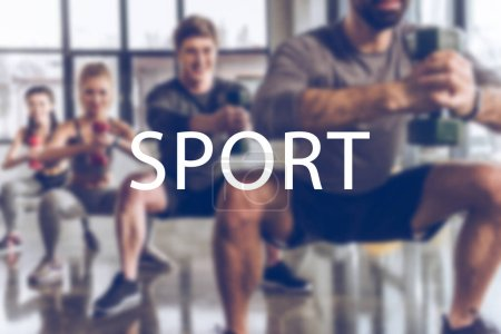 Photo for Blurred group of athletic young people in sportswear with dumbbells exercising at gym, sport inscription - Royalty Free Image