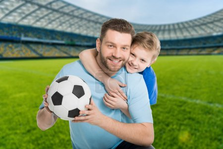 happy father an son with football ball on stadium