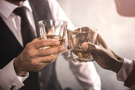 cropped shot of two men in formal wear clinking whiskey glasses